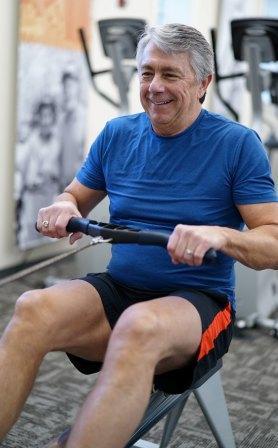 man in gymzaal aan het uit te oefenen terwijl hij glimlacht