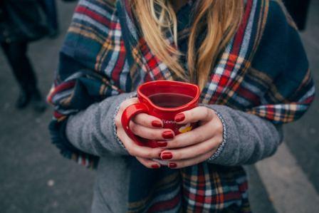een vrouw dracht handschoenen en houd een kopje