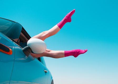 vrowu benen uit het raam van een auto